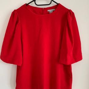 Pæn rød t-shirt/skjorte fra H&M. Fin detalje ved skulderen, der giver ærmerne lidt puf. Lynlås i nakken.