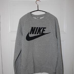 """Lækker, grå Nike-sweater. En """"herre"""" størrelse S, så kan bruges af de fleste.   Har et lille hul omkring det ene ærme, se det sidste billede."""