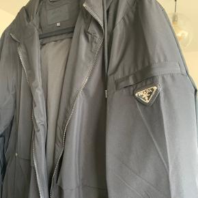 Prada nylon jakke med hætte. Er en str xL, men vil mene den passer en str m bedre, da modellen er slim fit. Købt på vestiaire til 4.000 kr.