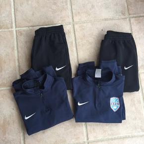 Trøjerne er marineblå; den ene med logo Bukserne er sorte; det ene par har en løbetrøje på en halv cm på underbenet