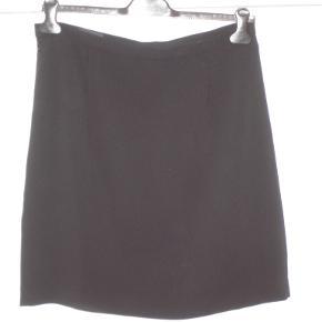 Klassisk, kort, stram, kulsort, nederdel fra SAND med foer, kort lynlås bagpå og i 100% ren uld og topgod pasform. Linningen måler 77 cm, og længden er 53 cm. En klassiker. Brugt 1 enkelt gang og fremstår ny. BYTTER IKKE!