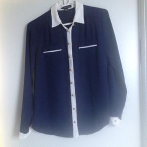 Fin mørkeblå skjorte med guld knapper i str 38. Brugt 1 gang.  Kan hentes i Nørresundby eller sendes på købers regning
