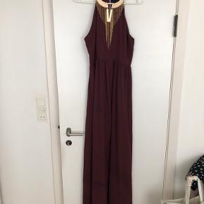 """Smukkeste kjole fra H&M exclusive linje. Kjolens farve er en flot dyb Bordeaux og har """"indbygget"""" guld smykke i kjolens hals.  Brugt én gang i forbindelse med gallafest."""