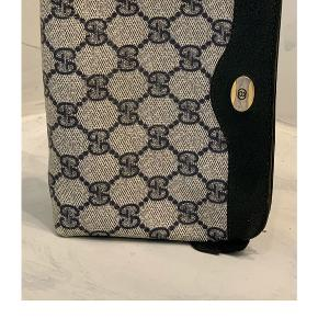 GUCCI • SMALL CLOTH PURSE. 800,- Den fineste lille sag fra Gucci i klassiske monogram med mørkeblå/sort læder og lille logo i sølv og guld. Den fremstår uden huller, dog er hjørnerne faded som kan ses på billederne Mål: B 18 cm H 12,5 cm