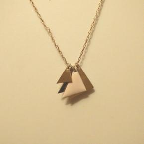 Så fin og unik guldhalskæde fra franske Titlee med vedhæng, som er fire trekanter guld og en i cremefavet emalje. Kæden måler 45 cm. Byd gerne :)