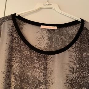 Flot gennemsigtig tunika med bådhals og rib i hals/ærme. 100% polyester og dejlig let at have på under en jakke eller om sommeren som smart top.