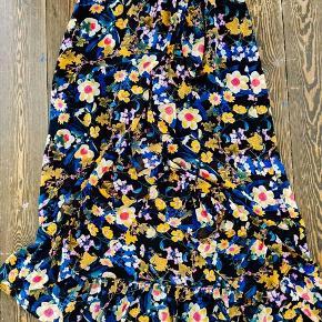Smuk, blomstret nederdel med høj slids foran og flæsekant. Kort underskørt i sort inderst.