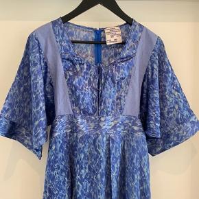 Smuk hellang kjole i blå nuancer. Fine detaljer omkring lommerne samt ved skuldrene med et bredt bånd. Let og lækker at have på med semi-blankt skær. Materiale: Blanding af silke, bomuld og polyamid.