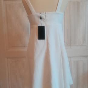 Sommerkjole, Fashion Union, str. M, hvid/offwhite, 100% Polyester, Ubrugt Feminin og klædelig med sløjfe foran og lynlås bagpå i et fint vævet-agtigt stof. Helt ny og ubrugt med mærkesedler. Den er også anvendelig som konfirmationskjole. Den er normal i størrelsen. Længde målt fra øverst på skulderstroppen og ned er cirka 86 cm. Nypris: 379 kr. Eventuel fragt lægges oveni.