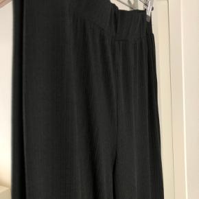 Løse bukser i ribbet stof, og med elastik i livet. Bagpå er der gået et par syninger op.