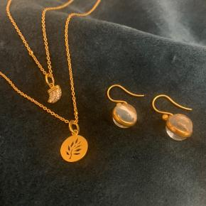 Julie Sandlau smykke sæt bestående af (inkl. ny pris) 2 kæder: 80 cm (1850,-) 60 cm (1400,-) To små zirkonia på hver kæde.   2 vedhæng: Tree of Life (500,-) Eagle (750,-)  1 sæt ørehængere  Prime m. Klar sten (1050,-)  Sterling sølv forgyldt med 22 karat guld.   Kan købes samlet eller hver for sig.  Samlet pris 2800,-  Pris pr del:  Kæde 80 cm 1050,- Kæde 60 cm 800,- Vedhæng Tree of Life 280,- Vedhæng Eagle: 425,- Ørehænger Prime m. Klar sten: 600,-