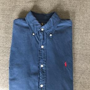 Klassisk slim fit skjorte i str. M fra Ralph Lauren. Den er brugt 3-5 gange og fremstår som ny.