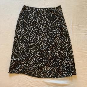 Sort og hvid prikket nederdel i knæ længde og med lynlås i taljen Brugt 1 gang