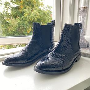 """- Sorte læderstøvler med """"slange"""" skind/print  - Elastik og hæl på 3 cm  - Ingen store tegn på slid udover sidste billede"""