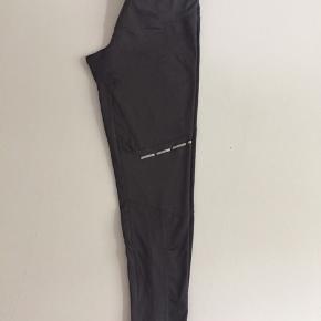 Mørkegrå bukser med neonfarvede detaljer og reflekser til løb eller fitness. De kan strammes ind i livet med en snor, der er en baglomme, og der er lynlås ved læggen. De er i perfekt stand, og ser ud som nye.   Varen befinder sig i KBH K.