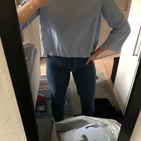 3/4 ærmet skjorte, med lynlås i nakken.  Den er lille i størrelsen.
