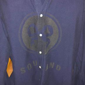 Mørkeblå soulland skjorte med logo på maven sælges. Fejler intet