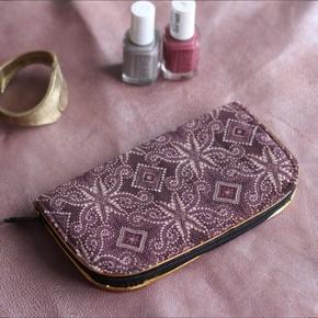 Clutch i lilla/bordeaux mønster.  Måler 18x10 cm