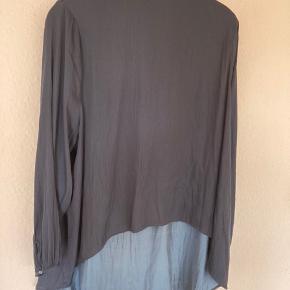 Flot bluse i fast stof. Bryst 2x72 Længde bag: 92 og foran 60.