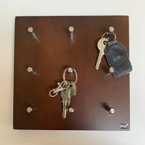 Square nøglebræt i træ med plads til 9 sæt nøgler. Aldrig brugt. Inklusiv skruer i original emballage.Måler: 20x20 cm Mærke: PO:Selected
