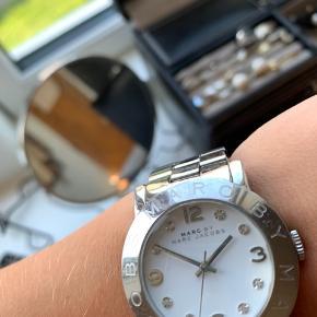 Ur fra Marc Jacobs Dameur 36mm stål - købt i 2014 og brugt en del, men har ligget i en skuffe i flere år, så det er stadig pænt. Tegn på slid er blandt andet ridser omkring urskiven, ved låsen og rundt på remmen. Trænger til at få skiftet batteri.