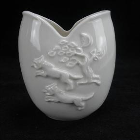 Varetype: Blanc De Chine Vase Med Relief Størrelse: 9 Farve: Hvid  Smuk lille blanc de chine vase med relieffer fra Royal Copenhagen.  Vasen måler 9 cm i højden og har nummer 20497.  2. Sortering i flot stand. Se billederne.  Kan sendes for 40 kroner.  Ingen byttehandel tak