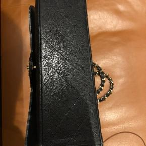 Sælges for min veninde. Chanel maxi double flap bag, caviar.  Tasken har guld hardware og er købt vintage i januar 2020. Oprindelig kvittering og certifikat haves og medfølger. Tasken har brugsspor indvendigt samt på hjørner udvendigt men er stadig velholdt. Mål :  Højde 22 cm Bredde 33 cm Dybde 9 cm Rem kan bæres på skulderen eller crossbody.