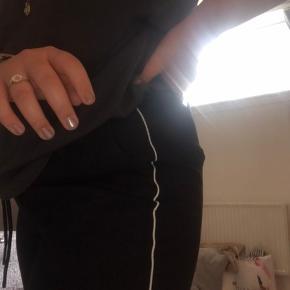 Sorte kontor lignede bukser, i blødt materiale med en hvid streg ned langs benet. Str. XL