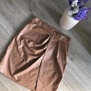 """Virkelig fin nederdel som jeg desværre aldrig har fået gået med 🤍 Str M. Den har sådan en """"slå om"""" kryds effekt, se billede to.   I en rigtig flot lysebrun farve og læder look a like 🤍🕊  50,-"""
