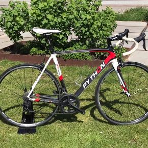 Racercykel - Python RF - C502i Team Edition, str. 57  Super lækker caboncykel til nybegynderen eller den mere øvede. Sælges grundet køb af ny.   Cyklen er af det danske mærke Python (Danmarks mest vindende cykelmærke), cyklen er fra december 2014. Den har altid været opbevaret inddørs og har kun nogle få Kosmetiske skrammer (Se billeder, flere billeder kan sendes)   Cyklen har kørt 4500 km, kæde og kassette dog under 200 km. Den står med fuld Shimano 105, 11 speed gruppe, 11-28 kassette og DTSWISS R24 spline hjulsæt, sælges ellers som den ses på billederne.   Står du og mangler en super lækker begyndercykel, eller vil du tage springet fra alu til kulfiber ramme, så er her en oplagt mulighed for at erober de danske landeveje på netop sådan en cykel uden at skulle smide hele sin formue efter det.