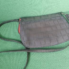 Fin lille taske med Betty Boo motiv i faux læder. Måler ca 24x19 cm. 2 nitter er faldet af som ses på billedet men jeg synes ikke det er noget man ligger mærke til. Remmen kan justeres i længden eller helt tages af så tasken bruges som clutch