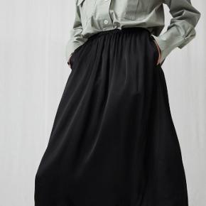 A-formet 'washed satin' nederdel med elastik i livet og sidelommer. I butikker/hjemmesiden nu. 100% Viskose   Sælger den, da jeg ikke får den brugt.