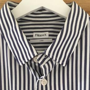 Lækker blød skjorte fra Filippa K med mørkeblå striber. Næsten ikke brugt.   Model er 189 høj og bruger normal L/xl i overdele