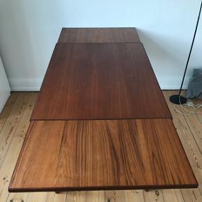 Lille spisebord i teaktræ med udtræk i begge sider.   Længden uden udtræk er 104 centimeter, og med udtræk er længden 187 centimeter.   Bredden er 74 centimeter.   Højden er 71 centimeter.