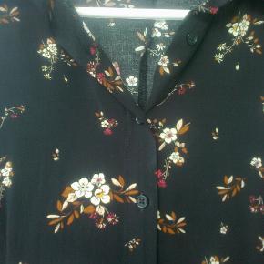 Varetype: maxi kjole med blomster maxikjole Farve: Brun blomstret blomster  Maxikjole med knapper hele vejen ned foran.  3/4 ærmer 100 % viskose Sendes forsikret med dao mm andet aftales