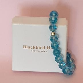 Meget smukt turkis/blåt armbånd i krystal og guld fra Blackbird Hill Copenhagen. Elastisk.
