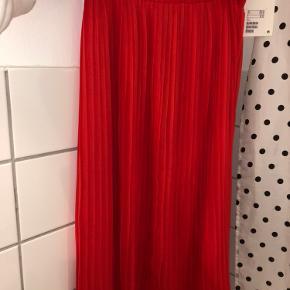 Orange/rød plisseret nederdel. Aldrig brugt. Stadig med prismærke  BYD