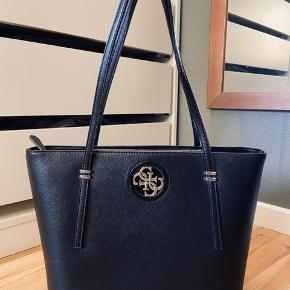 En sort Guess taske. Jeg brugte den, som skole taske nogle dage. Men fandt desværre ud af, at den ikke rigtig var mig alligevel. Der er ikke nogle store fejl eller noget der falder i øjnene. Man kan se, at den har været i brug. En taske jeg godt selv ville kunne finde på, at købe i forhold til standen (Evt BYD)
