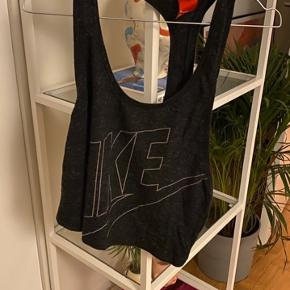 Grå sports crop top fra NIKE i str. M. Brugt to gange.  Se mine andre annoncer for mere træningstøj fra NIKE og Reebok.   Søgeord: træningstop træningstøj sportstop sportstøj