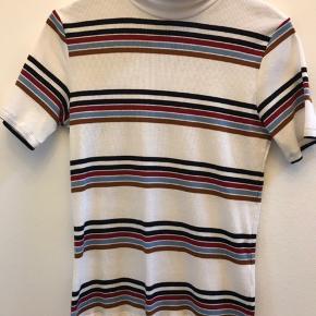 Strikket kortærmet bluse med striber i flere farver  og høj hals.  Polyster, viscose og elastane Ingen bytte Fast pris ex lev.