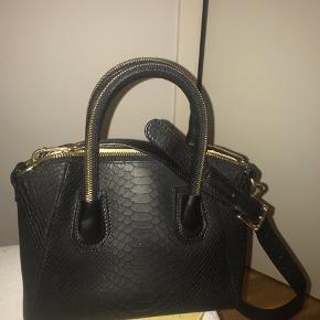 Fin sort slangeprint håndtaske/skuldertaske med aftagelig skulderrem fra Leowulff.  Tasken er i fint stand.  Kan hentes i Kbh SV eller sendes på købers regning.