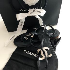 Flotte flade læder sandaler fra Chanel med ankelrem. Sort læder med sølv hardware.   Str 37,5 men jeg synes at de er små i str så vil mene at str 37 også passer dem.   De er brugt nænsomt og standen GMB er alene sat fordi man kan se at de har været i brug under den udvendige lædersål ligesom det påtrykte Chanel mærke i den indvendige sål på hælen er en smule slidt af - ellers i meget fin stand og har altid været opbevaret i dustbag.  Dustbag og pose medfølger om man vil.   Sandalerne er flere sæsoner gammel og har ikke gemt kvitteringen/æske - men mener at de kostede lige omkring DKK 4000.   Bud er velkomne - køber betaler porto og gebyr men jeg handler gerne via mobile pay for at spare sidstnævnte.