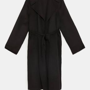 Lækker blød og let frakke i uldblanding. Lukkes med bælte (ingen knapper), har bred reverse og skjulte sidelommer. Ingen foer, så den er bedst som overgangsjakke eller til en mild vinter med en trøje under.  Minder om styles fra Ganni Str. L, fitter str. 36-40 alt efter hvor oversize man kan lide den :) Bytter ikke