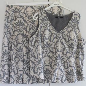 Silke: nederdel + bluse 100 % NY:  Lækkert sæt bestående af bluse + nederdel. Virkelig flot stof i 52 % silke + 48 % bomuld.  Farve: Sand + grå  Toppen har lynlås i siden.  Brystvidde: 57 cm x 2,  Hoftevidde: 60 cm x 2 Længde: 63 cm   Nederdelen har læg både foran og bagpå. Livvidde: 48 cm x 2 Længde: 68 cm  Både nederdel og bluse er med et tyndt foer.  Ingen byt, og prisen er fast