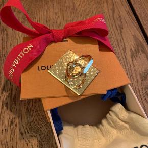 Sælger min Louis Vuitton phone ring i guld. Den er aldrig brugt og nu bliver den solgt da den bare ligger i æsken.   Alt medfølger æske , dustbag og kvittering.   Mp 1000kr