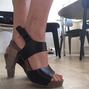 Sorte læder heels (10cm) med velcro lås omkring anklen .  Fortrudt køb - sidste sommer . De er super gode at gå i - ser godt ud med et par jeans eller en kjole .