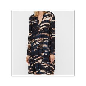 Bytter ikke.  Eksklusiv porto. Helt klassisk kjole i et smuk print fra GUSTAV i mørke nuancer. Helt klassisk kjole i et smuk print fra GUSTAV i mørke nuancer. Det er en løs model, har V-hals, med en enkelt knap, lidt vidde forneden, med side lommer. Lange ærmer med manchetter, lukket med en enkelt knap.    Kvaliteten er: 96 % viskose, 4% elasthan.  Normal i størrelsen. Farve: Som billede 1 og 2.  Gustav størrelsesguide str. 38: Bryst mål 92 cm Talje mål 76 cm Hofte mål 100 cm      For og bag stykket målt ved bryst linjen 114 cm. Længde fra skulder og ned 101 cm.  Kjolen er ubrugt. Kommer fra et ikke ryger og parfume frit hjem.