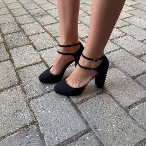 Høje stiletter med subtilt sort nitter på hælen. Kun prøvet på. Kan hentes i Århus og København efter aftale