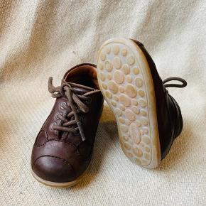Begyndersko fra Bisgaard i brun med høj og fast hælkappe, der giver god stabilitet og støtte.   Skoen er produceret i 100% naturligt og åndbart læder med en blød, fleksibel og skridsikker gummisål.  Justerbar snøre sikrer en optimal og naturlig pasform.  Pæn stand