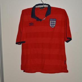 Varetype: fodbold trøjeStørrelse: Large Farve: Rød  Engelsk landholdtrøje  i rød velour  Kraven er blå men skal nok lige stryges  Trøjen er lidt forvasket men uden huller og i rimelig stand